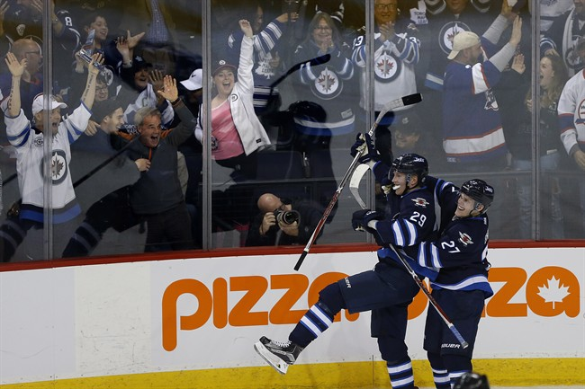 Winnipeg Jets' Nikolaj Ehlers (27) and Patrik Laine (29) celebrate Patrik Laine's (29) game winning goal and hat-trick during overtime against the Toronto Maple Leafs in NHL action in Winnipeg on Wednesday, October 19, 2016.