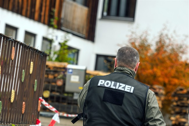 A policeman walks along the house in Georgensgmuend, Germany.