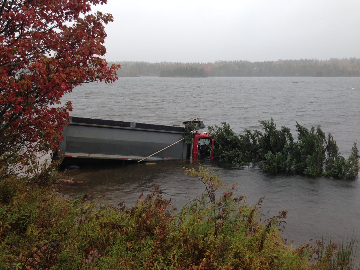 Dump truck crashes into Miller Lake; driver saved by passerby
