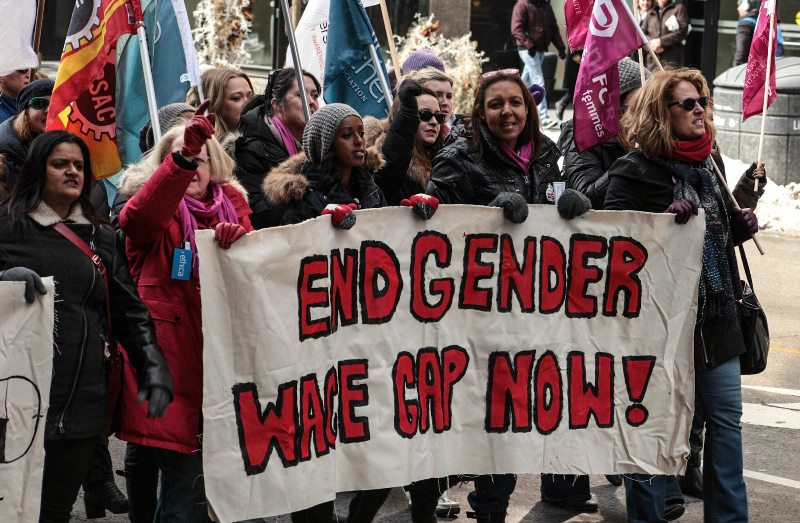 """Protesters in Toronto march behind a banner which reads """"End Gender Wage Gap Now!""""."""