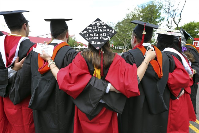 In this May 15, 2016 file photo, students embrace as they arrive for the Rutgers graduation ceremonies in Piscataway, N.J.