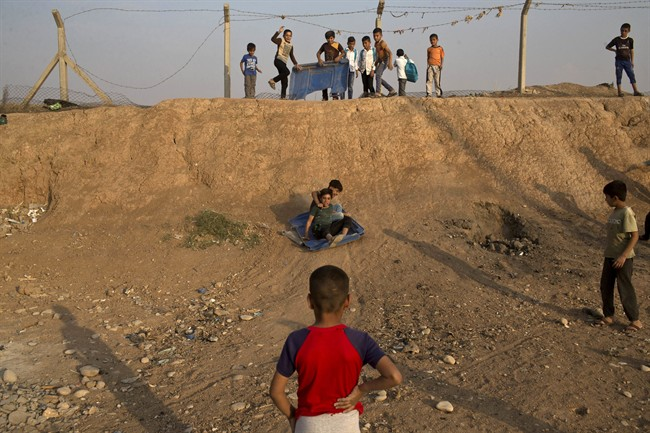 Children use a piece of plastic to slide down a slope at the Baharka camp for displaced persons on the outskirts of Irbil, Iraq, Tuesday, Oct. 25, 2016. Nearby Mosul, the largest city controlled by the Islamic State group, is still home to more than 1 million civilians. (AP Photo/Marko Drobnjakovic).
