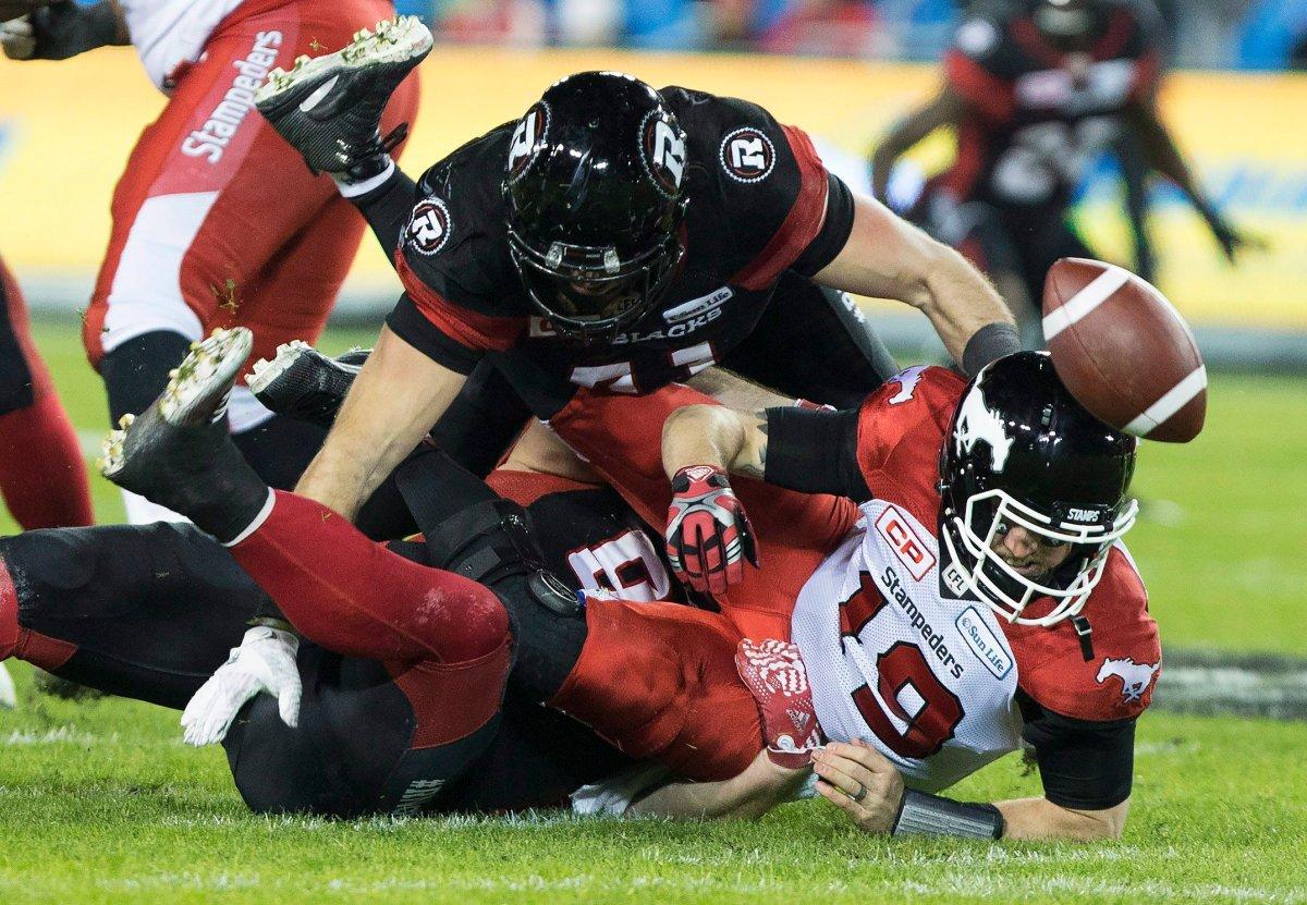 Calgary Stampeders quarterback Bo Levi Mitchell is sacked by Ottawa Redblacks defensive lineman Zack Evans, bottom and defensive end Arnaud Gascon-Nadon during third quarter CFL Grey Cup action Sunday, November 27, 2016 in Toronto.