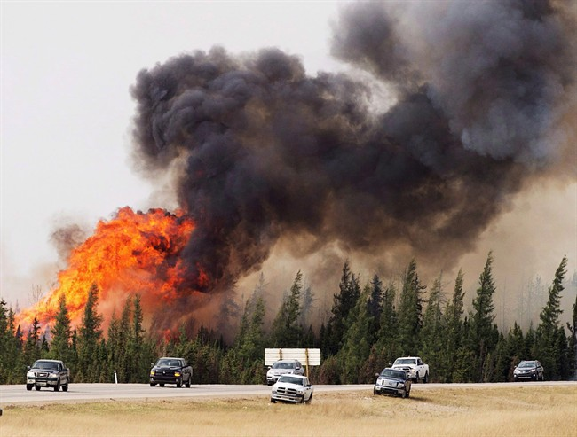 A convoy of evacuees from Fort McMurray, Alberta drive past wildfires that are still burning out of control as they leave the city Saturday, May 7, 2016.