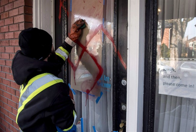 A graffiti removal worker cleans anti-Semitic graffiti, including a swastika, that was spray painted on the door of The Glebe Minyan in Ottawa, in this file photo.