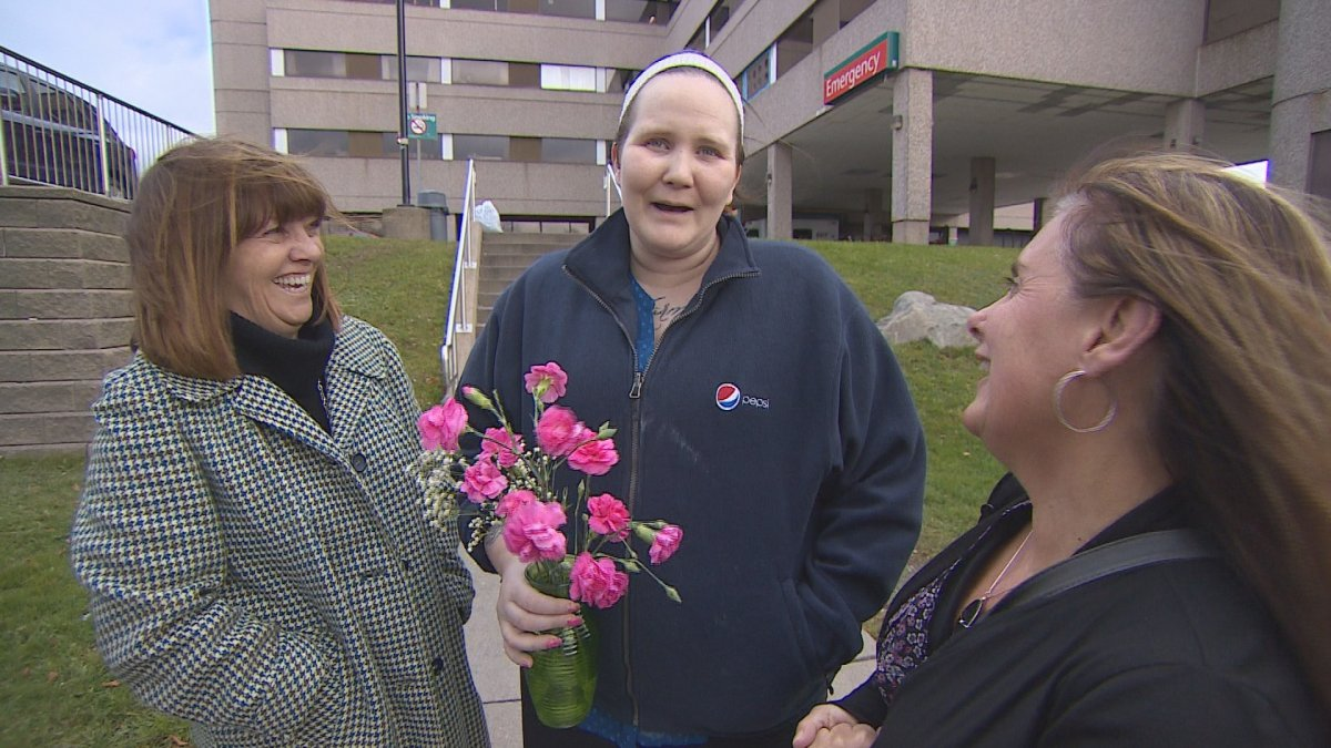 Fliss Cramman holds a bouquet flowers as she leaves the Dartmouth General Hospital on Nov. 23.