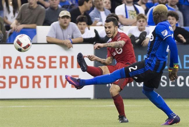 Montreal Impact's Ambroise Oyongo, right, challenges Toronto FC's Sebastian Giovinco during first half soccer action of the first leg of the MLS Eastern Conference final at the Olympic Stadium in Montreal, Tuesday, November 22, 2016. THE CANADIAN PRESS/Graham Hughes.