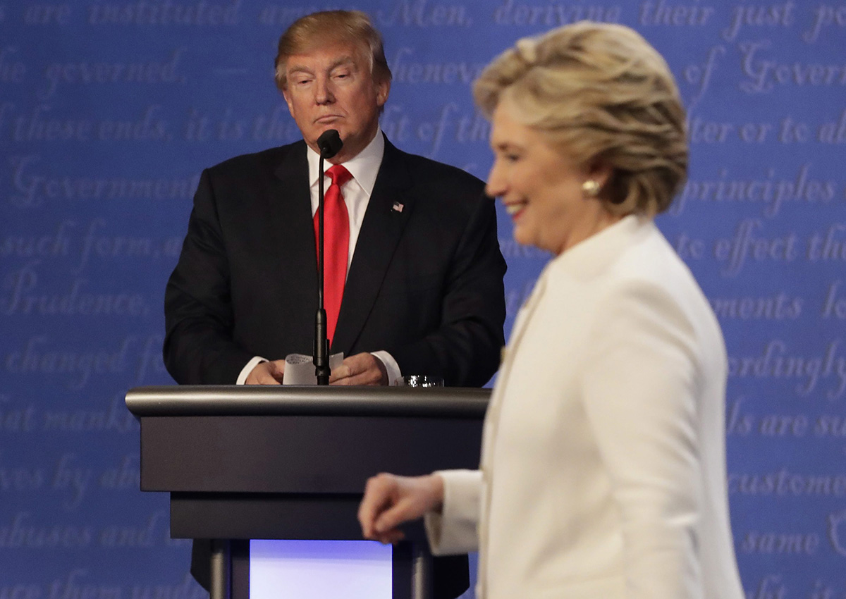 In this Oct. 19, 2016 file photo, Republican presidential nominee Donald Trump waits behind his podium as Democratic presidential nominee Hillary Clinton makes her way off the stage following the third presidential debate at UNLV in Las Vegas.