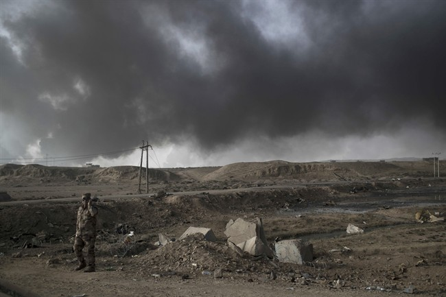 A Iraqi soldier stands near a checkpoint as smoke rises from burning oil fields in Qayara, south of Mosul, Iraq, Tuesday, Nov. 1, 2016.
