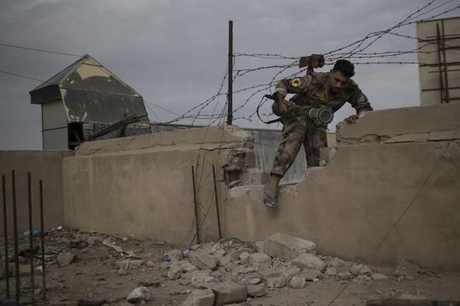 An Iraqi special forces fighter moves between buildings near the front line during fighting with Islamic State militants, in eastern Mosul, Iraq, Tuesday, Nov. 15, 2016. (AP Photo/Felipe Dana).