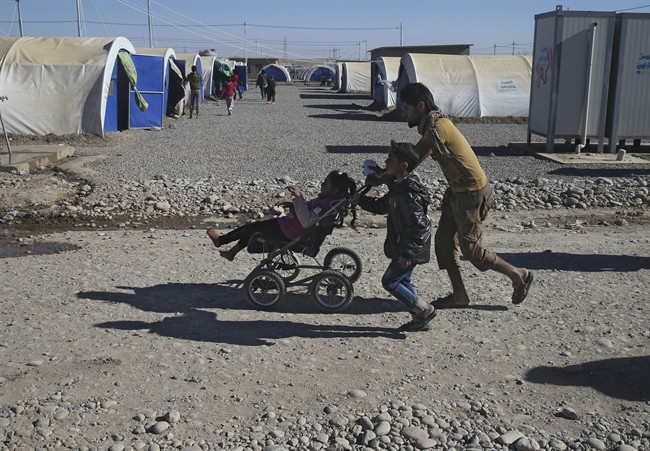 An Iraqi man who fled the fighting between Islamic State militants and the Iraqi forces, carries a handicapped girl at a camp for internally displaced people, in Khazer east of Mosul, Iraq, Monday, Nov. 21, 2016. Iraqi troops fighting Islamic State militants in the eastern outskirts of Mosul regrouped Monday in the city's neighborhoods they recently retook from the extremist group, conducting house-to-house searches and looking for would-be suicide car bombs, a top Iraqi commander said. (AP Photo/Hussein Malla).