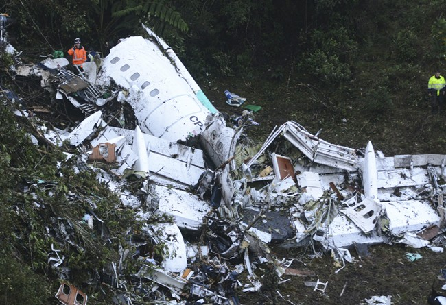 Rescue workers stand at the wreckage site of a chartered airplane that crashed outside Medellin, Colombia, Tuesday, Nov. 29, 2016. The plane was carrying the Brazilian first division soccer club Chapecoense team that was on it's way for a Copa Sudamericana final match against Colombia's Atletico Nacional.