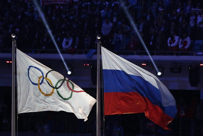 The Russian national flag, right, flies next to the Olympic flag during the closing ceremony of the 2014.THE CANADIAN PRESS/AP, Matthias Schrader.