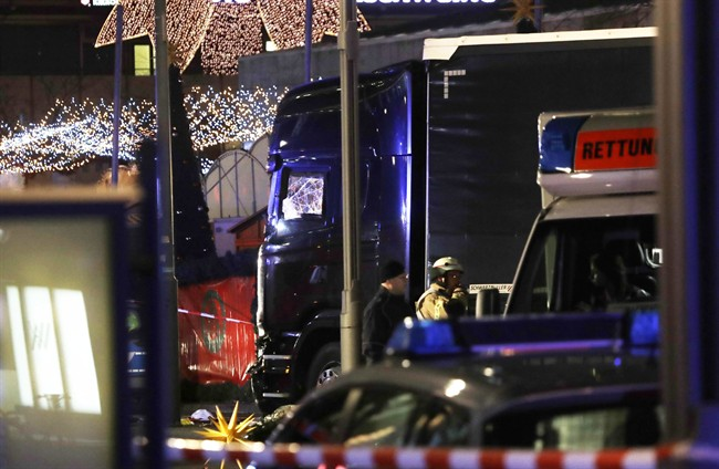 Police stand beside a damaged truck which ran into crowded Christmas market in Berliin Berlin, Germany, Monday, Dec. 19, 2016. (AP Photo/Michael Sohn).