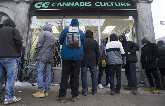 People wait outside Cannabis Culture in Montreal, Friday, December 16, 2016. If police catch you with pot before July 2018, you can still face charges.