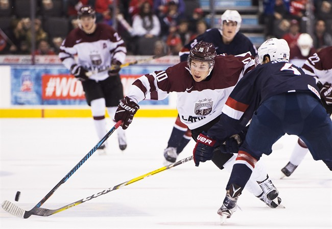 Latvia's Martins Dzierkals (10) drives past the United States' Caleb Jones (4) during third period IIHF World Junior Championships in Toronto on Monday, December 26, 2016. THE CANADIAN PRESS/Nathan Denette.