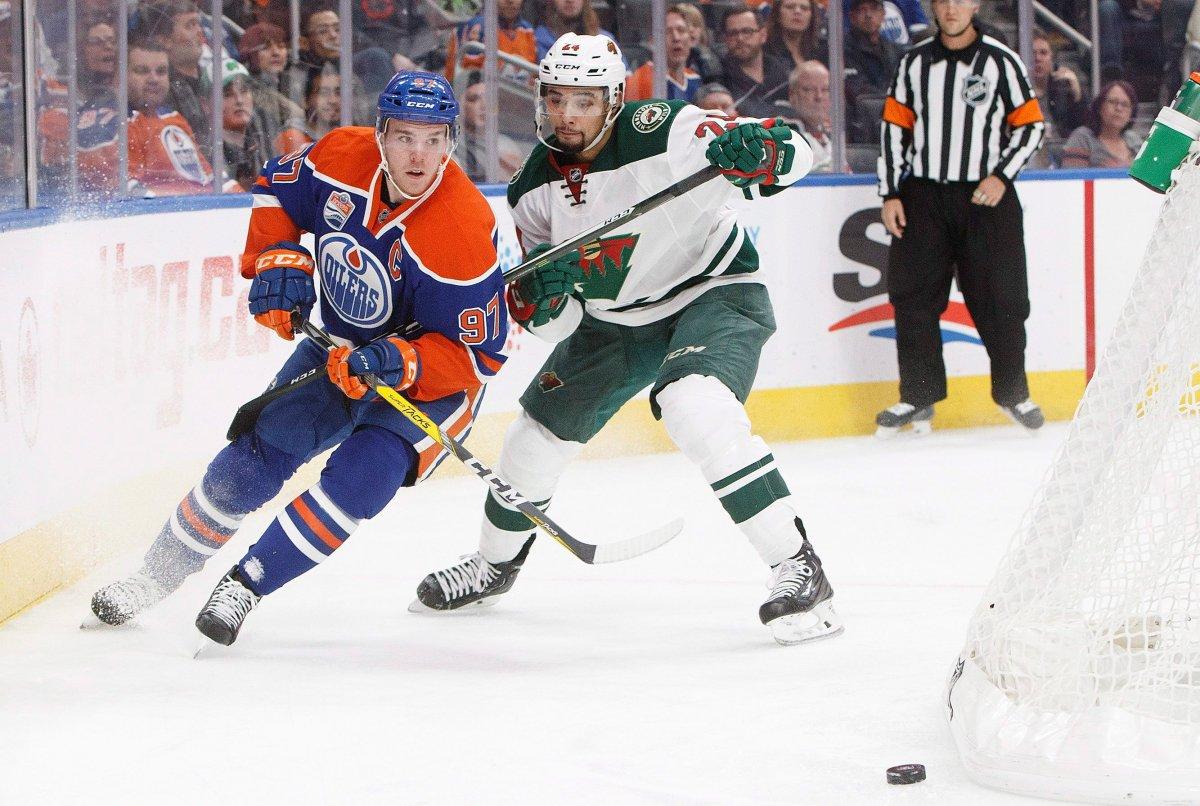 Minnesota Wild's Matt Dumba (24) defends against Edmonton Oilers' Connor McDavid (97) during second period NHL action in Edmonton, Alta., on Sunday December 4, 2016. THE CANADIAN PRESS/Jason Franson.