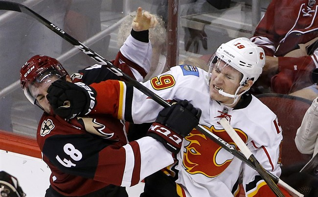 Calgary Flames left wing Matthew Tkachuk (19) mixes it up with Arizona Coyotes left wing Jordan Martinook (48) during the second period of an NHL hockey game Thursday, Dec. 8, 2016, in Glendale, Ariz.