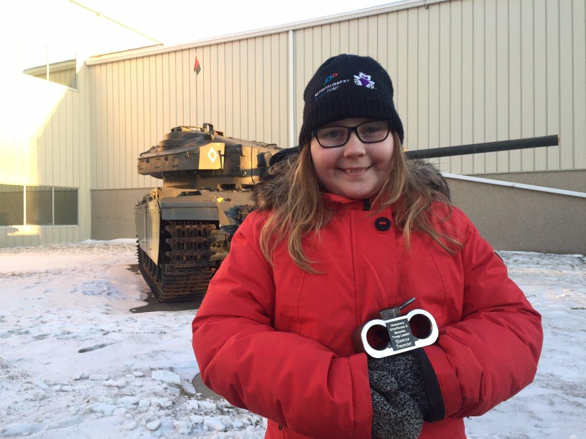 Rheanna Trepanier, 10, holding her handmade tank after riding in a tank at the Edmonton Garrison.