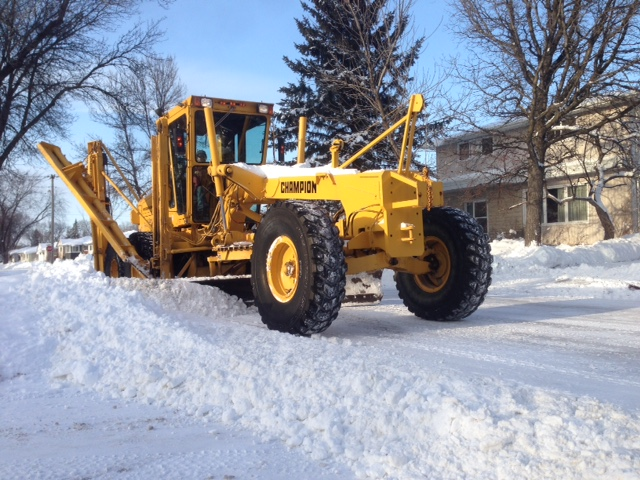 A grader plows a Winnipeg street.