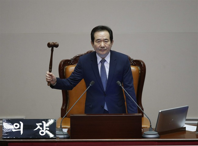South Korea's Assembly Speaker Chung Sye-kyun presides over a plenary session to vote on the impeachment bill of South Korean President Park Geun-hye at the National Assembly in Seoul Friday, Dec. 9, 2016. South Korean lawmakers on Friday impeached Park, a stunning and swift fall for the country's first female leader amid protests that drew millions into the streets in united fury. (Kim Hong-Ji/Pool Photo via AP).