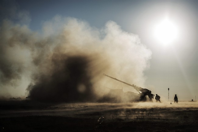 French soldiers shoot a canon toward Islamic State militant positions from a coalition forces military base in Qayara, Iraq, Saturday, Dec. 10, 2016. Teams are poised to prevent the spread of Islamic State fighters after the Iraqi city of Mosul falls.
