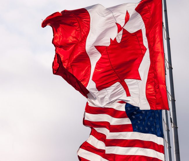 Canadian and American flags fly beside each other in Sarnia, Ont., Oct. 18, 2016.