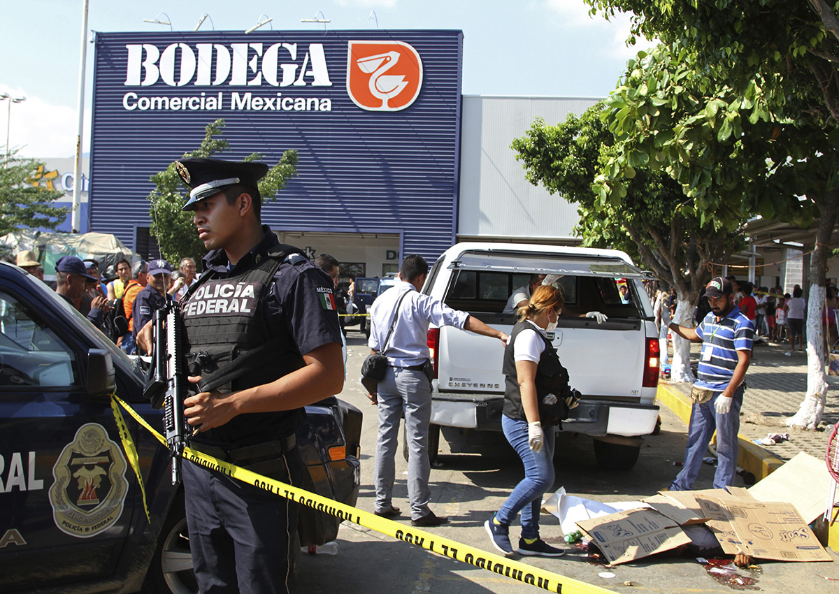 Police and forensics secure the area where six people lie dead, two of them covered with cardboard at right, in Acapulco, Mexico, Wednesday, Jan. 4, 2017.