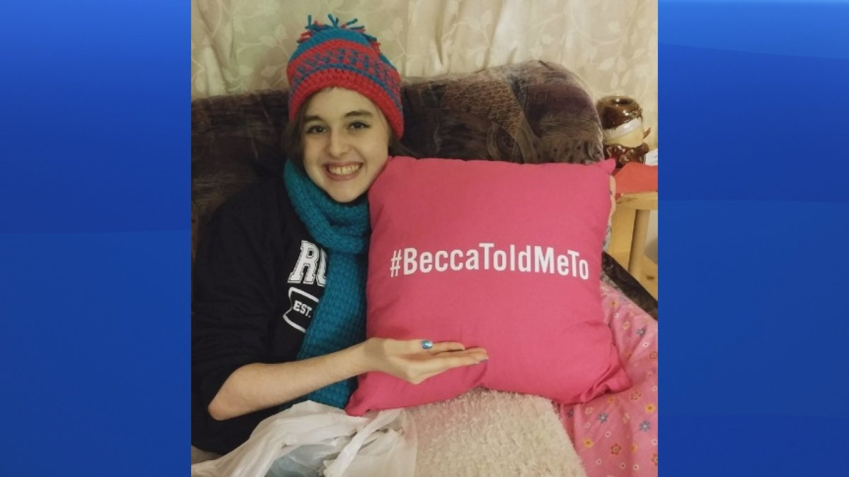 Becca Schofield, a Riverview, N.B. teenager battling terminal brain cancer, holds a pillow with a hashtag she asked people to use in December to chronicle when they performed acts of kindness in her honour.
