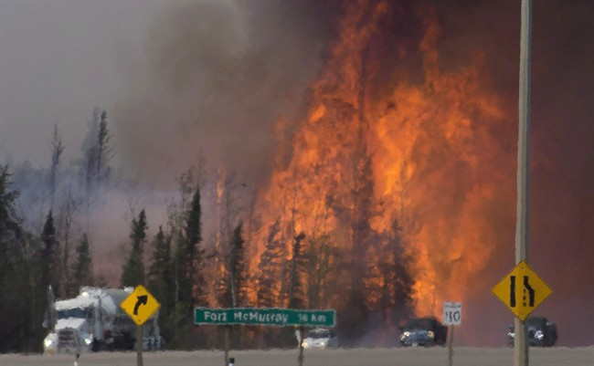 """Heat waves are seen as cars and trucks try and get past a wild fire 16km south of Fort McMurray on highway 63 Friday, May 6, 2016. The """"beast"""" of a wildfire that charred Fort McMurray, Alta., was named Canada's biggest weather story of the year in an annual list compiled by the country's top meteorologists."""