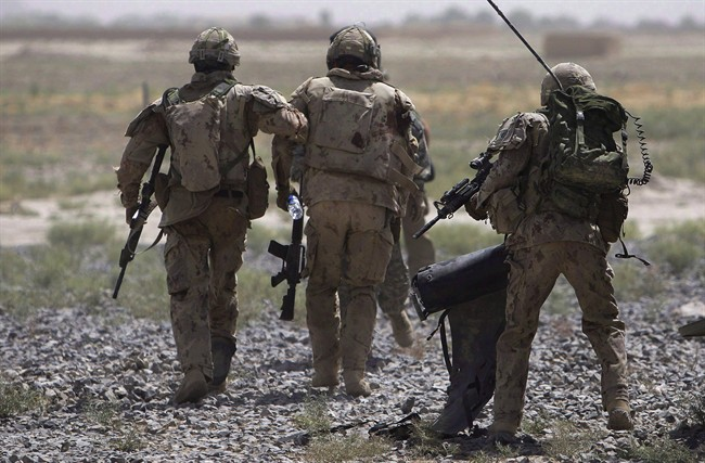 Canadian soldiers help a comrade, center, get on a helicopter after he was injured in an IED blast during a patrol outside Salavat, in the Panjwayi district, southwest of Kandahar, Afghanistan, Monday, June 7, 2010.