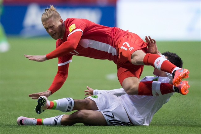 Canada's Marcel De Jong, top, is tackled by Mexico's Hirving Lozano during first half FIFA World Cup qualifying soccer action in Vancouver, B.C., on Friday, March 25, 2016.