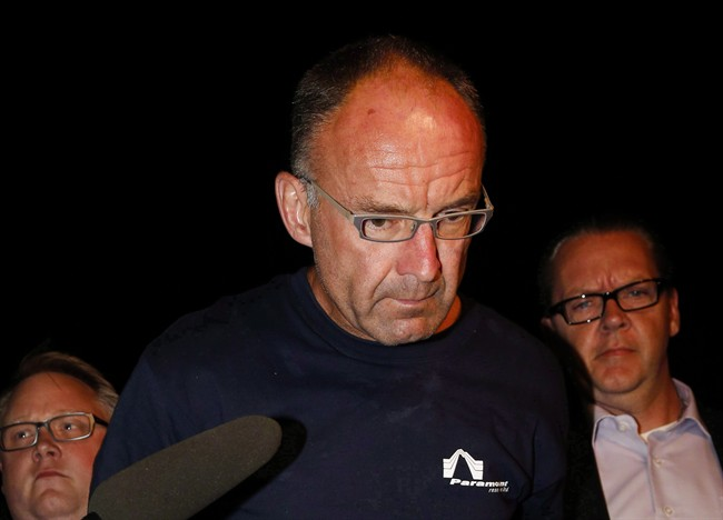 Douglas Garland is escorted into a Calgary police station in connection with the disappearance of Nathan O'Brien and his grandparents in Calgary, Alta., on July 14, 2014.