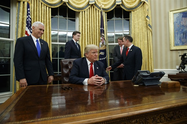 Vice President Mike Pence, left, watches as President Donald Trump prepares to sign his first executive order, Friday, Jan. 20, 2017, in the Oval Office of the White House in Washington. (AP Photo/Evan Vucci).