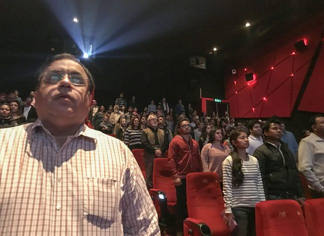 Audience members stand for the Indian national anthem before a movie starts at a cinema in New Delhi on December 4, 2016.