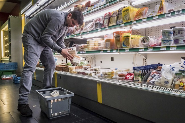 """A worker removes expired food in a local supermarket in Brussels on Monday, Jan. 16, 2017. The European Court of Auditors has chided the European Union's executive branch in a report, """"Combating Food Waste,"""" that decries the bloc's lack of effort in reducing the food waste, estimating the EU wastes 88 million tons of food per year. (AP Photo/Geert Vanden Wijngaert)."""