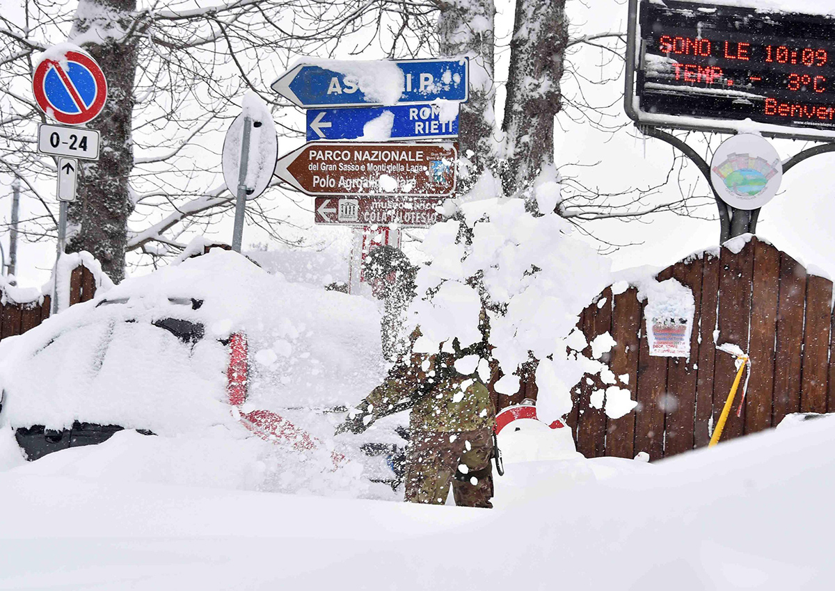 A soldier shovels snow in Amatrice, central Italy, Wednesday, Jan. 18, 2017.