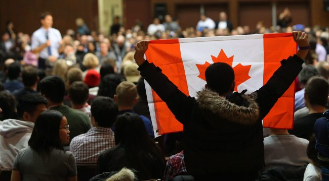 An audience member holds a Canadian Flag as Prime Minister Justin Trudeau speaks during a town hall meeting at Alumni Hall, Western University on Friday, Jan. 13, 2017, in London, Ontario.