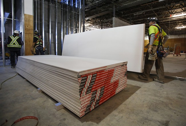 Construction workers move sheets of drywall at a building project in Calgary, Alta., Friday, Dec. 30, 2016. Anti-dumping duties on U.S. drywall imports into Western Canada have hiked prices for the building product but have also resulted in new manufacturing jobs, says the company whose complaint prompted the trade tariffs. CertainTeed Gypsum Canada has added about 30 employees since duties began in September at its drywall plants in Vancouver, Calgary and Winnipeg to boost production, said spokesman Mike Loughery in an email.