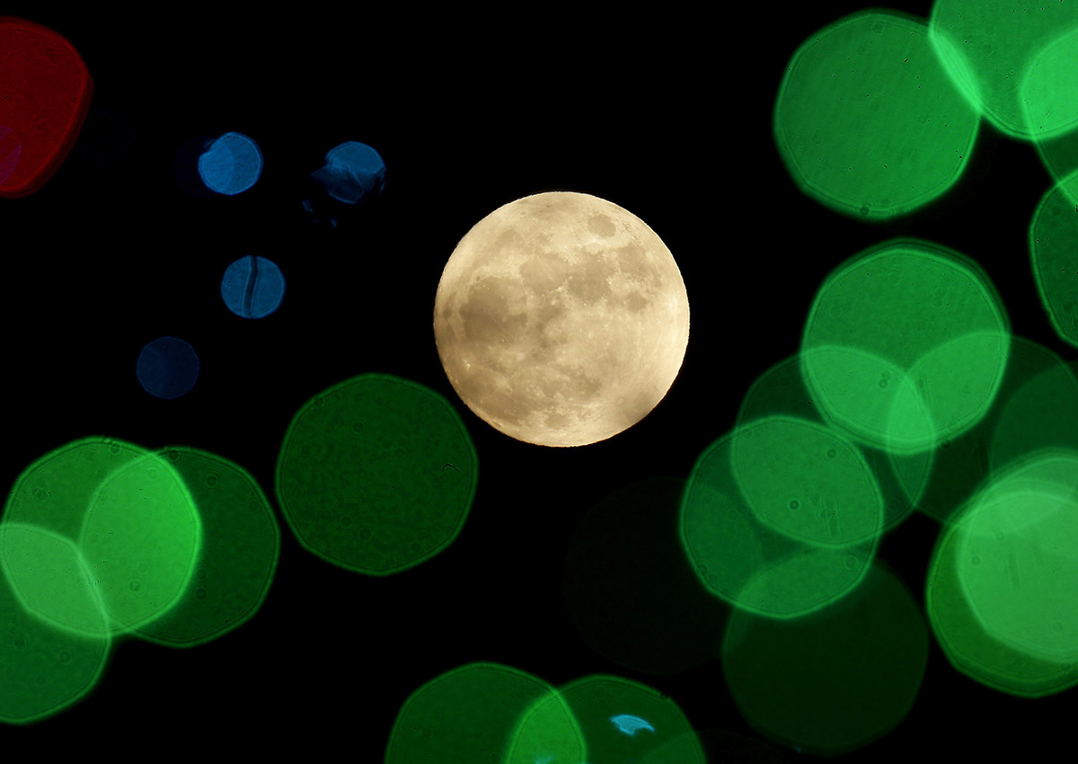 In this Thursday, Dec. 24, 2015, file photo, a nearly-full moon is seen among Christmas lights at a holiday display near Lenexa, Kan.