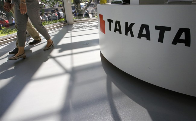 In this May 4, 2016 file photo, visitors walk by a Takata Corp. desk at an automaker's showroom in Tokyo.