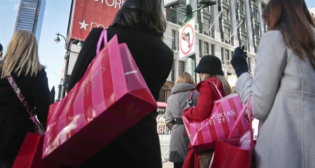 FILE - In this Saturday, Nov. 23, 2013, file photo, shoppers carry Victoria Secret bags while crossing an intersection in Herald Square in New York.