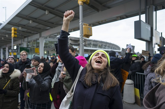 A protester raises her fist and shouts as she joins others assembled at John F. Kennedy International Airport in New York, Saturday, Jan. 28, 2017 after two Iraqi refugees were detained while trying to enter the country. On Friday, Jan. 27, President Donald Trump signed an executive order suspending all immigration from countries with terrorism concerns for 90 days. Countries included in the ban are Iraq, Syria, Iran, Sudan, Libya, Somalia and Yemen, which are all Muslim-majority nations. (AP Photo/Craig Ruttle).