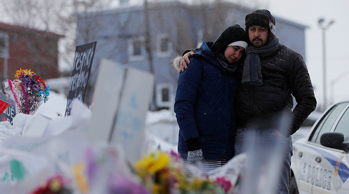 In this file photo, Azzedine Najd and his wife Fadwa Achmaoui look at the memorial near the site of a fatal shooting at the Quebec Islamic Cultural Centre in Quebec City on January 31, 2017.