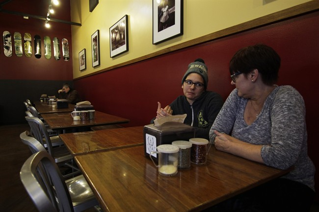 In this Jan. 9, 2017, photo, Andrea Ledesma, 28, second from right, talks with her mother, Cheryl Romanowski, at Classic Slice pizza restaurant, where Ledesma works, in Milwaukee.