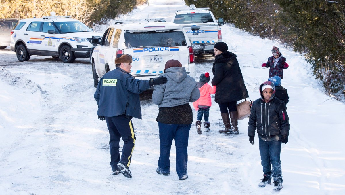 Family members from Somalia are escorted to waiting vehicles by RCMP officers following their crossing into Canada over the U.S.-Canada border near Hemmingford, Que., on Friday, February 17, 2017. A number of refugee claimants are braving the elements to illicitly enter Canada.