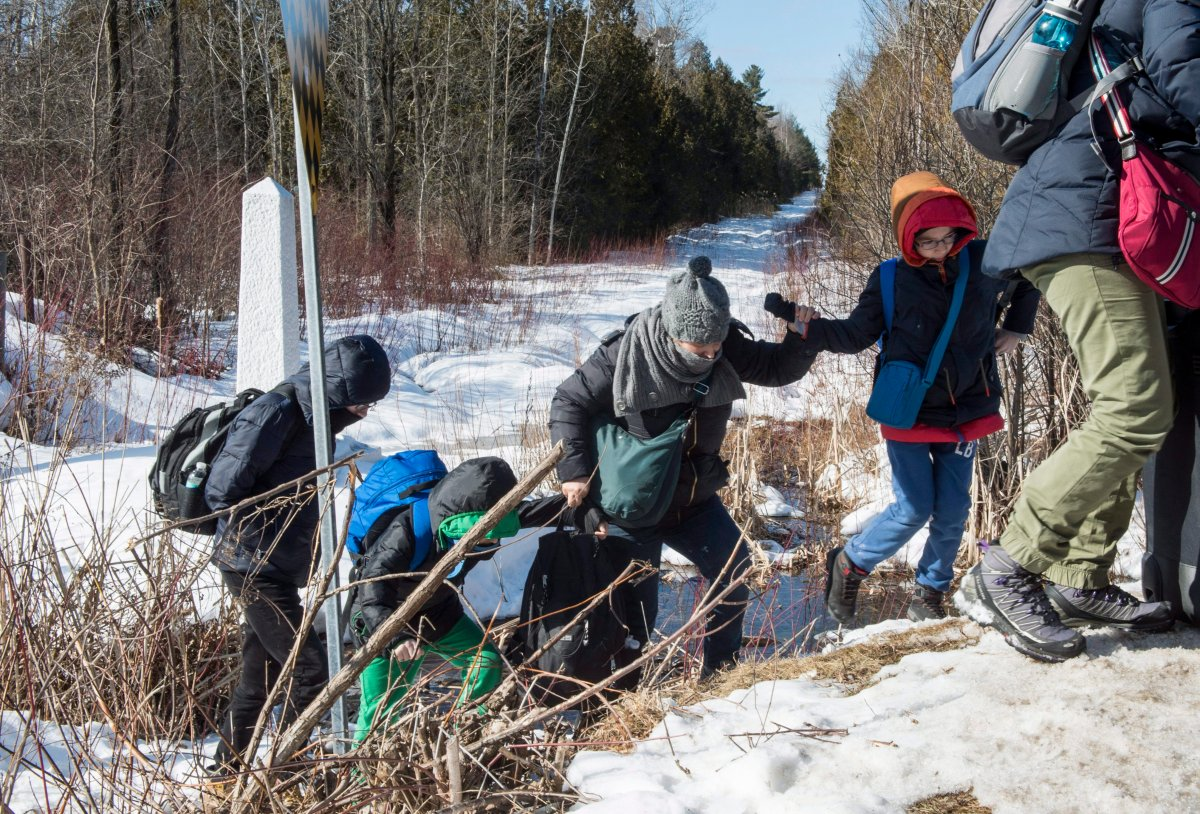A family of asylum claimants walks across the border into Canada from the United States in February 2017.