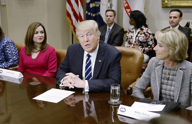 U.S. President Donald Trump, flanked by Education Secretary Betsy DeVos (right) speaks during a parent-teacher conference listening session at the White House in Washington, DC.