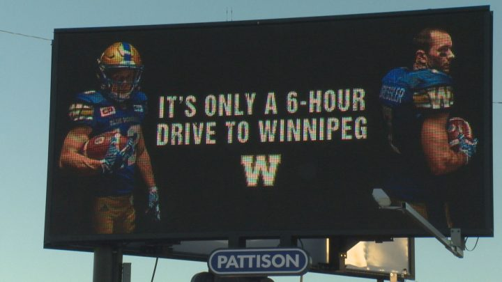 The billboard that the Winnipeg Blue Bombers put up on the corner of Dewdney Avenue and Lewvan Drive shows an image of former Rider receivers Weston Dressler and Ryan Smith beside text letting people know that Winnipeg is only a six hour drive from Regina.