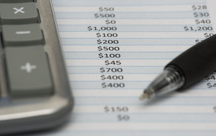 A calculator, expense sheet and a pen are shown.